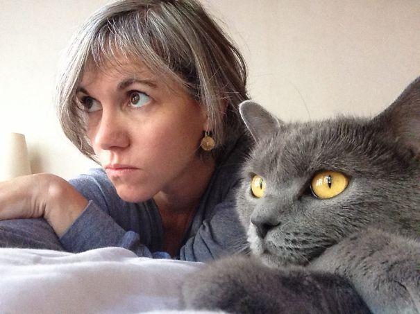 gato y mujer con ojos grandes miran con sigilo hacia el horizonte