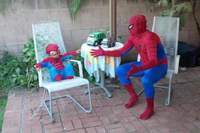 padre e hijos disfrazados de spiderman sentados en un jardín casero