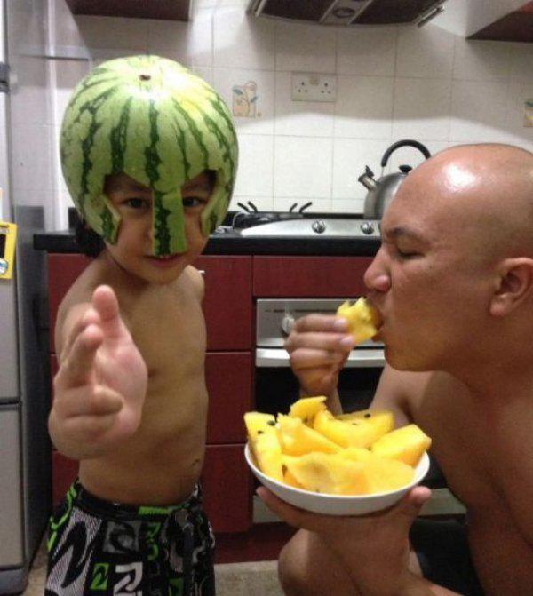 papa come piña mientras hijo posa con casco de sandía