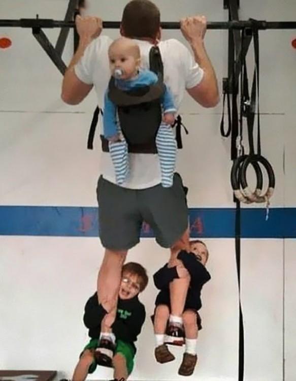 padre se jercita mientras carga a sus hijos en espalda y piernas