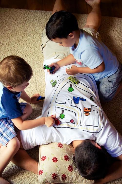 papa se pone playera en forma de camino para entretener a sus hijos mientras toma una siesta