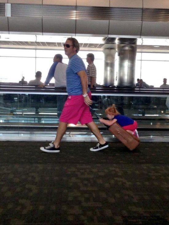 papa lleva sobre la maleta a hija mientras la arrastra como carrito