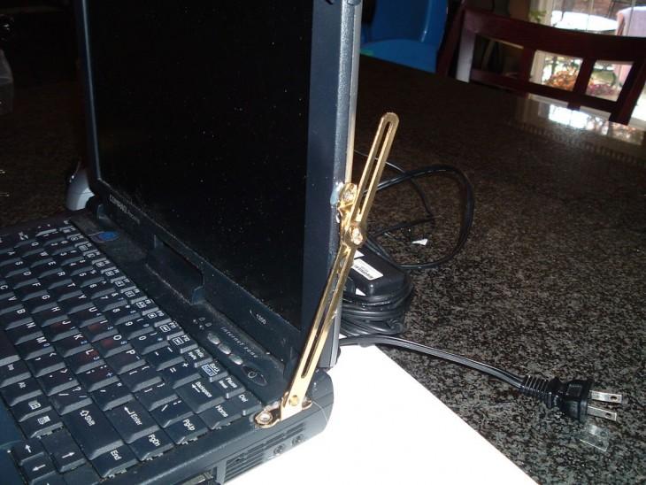 antigua laptop es remendada con un sujetador al parecer de un mueble para abrir y cerrrar sin que esta se cierre y se rompa la pantalla
