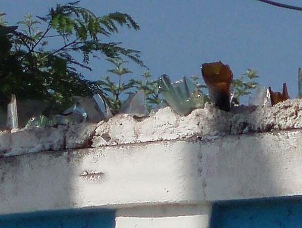 Botellas de vidrio que fueron colocadas para evitar que entren en sus propiedad por las bardas
