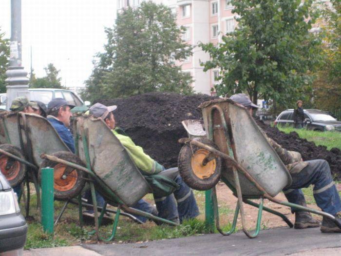 Hombres descansando sobre las carrtillas utilizadas como asientos en medio de la construcci+on