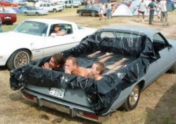 alberca improvisada en la parte trasera de una camioneta con tres sujetos en su interior bañándose