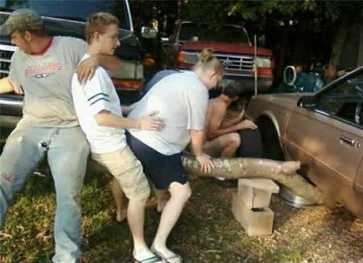 familia ayuda a hombre a cambiar una llanta con un tronco siendo utilizado como gato hidraulico