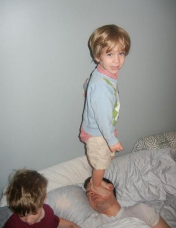 nilo sobre la cabeza de su papá para que se despierte a jugar con él