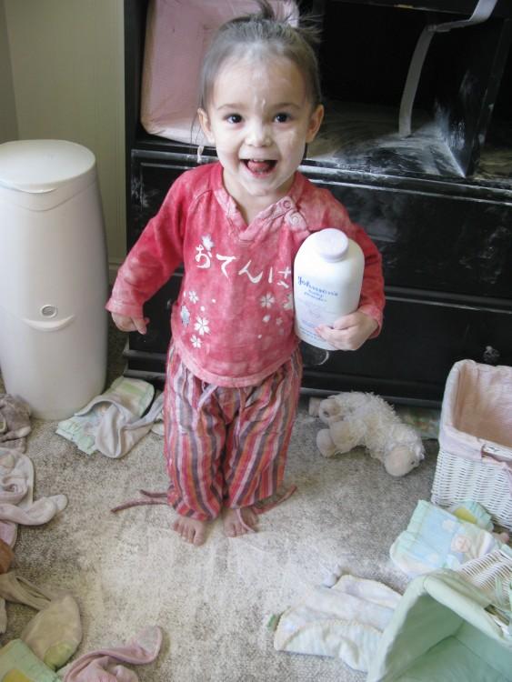 niña jugando con el talco en su habitación feliz de haberlo esparcido por todo el lugar