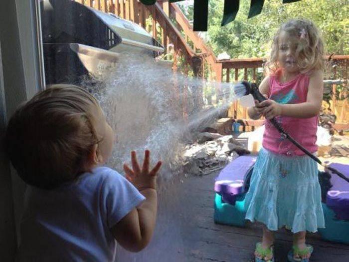 niña avienta agua sobre el vidrio de la puerta para jugar con su hermanito
