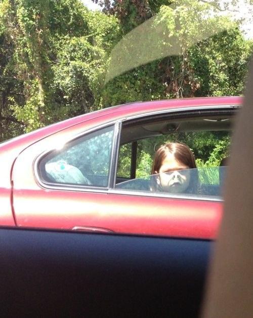 niña haciendo nariz de cerdo sobre el cristal del carro