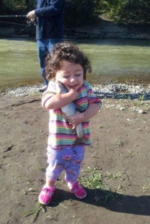 niña abranzado a pescado muy feliz