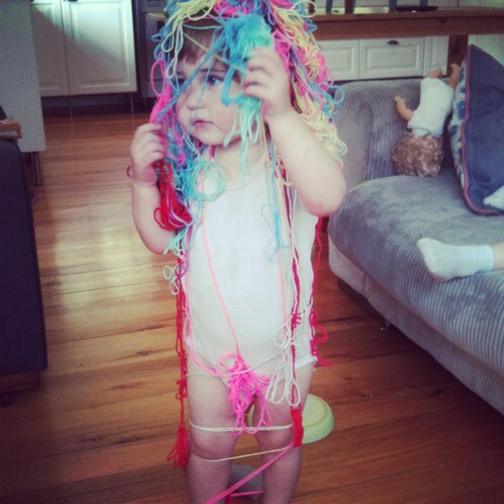 niña enredada en el estambre de colores