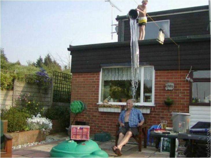 niño travieso sube al techo y tira agua del cubo sobre cabeza del abuelo