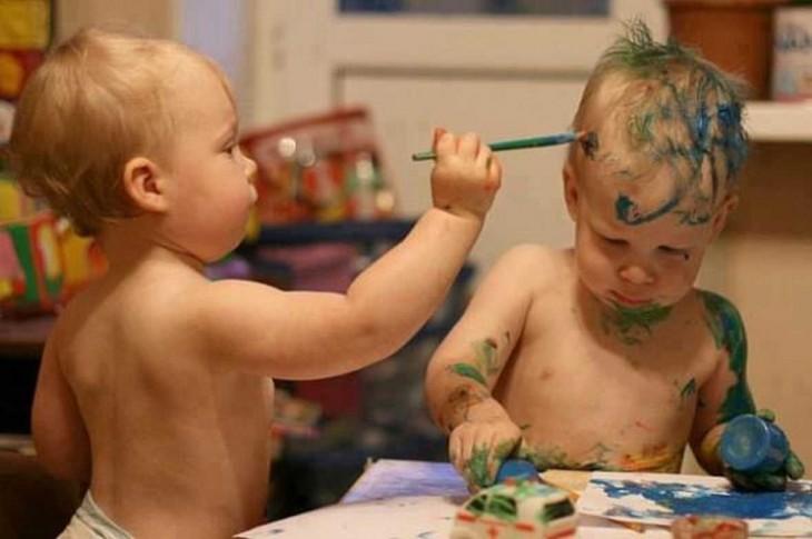 hermanito gemelo pintando la cara de su otro hermano con un marcador o brocha