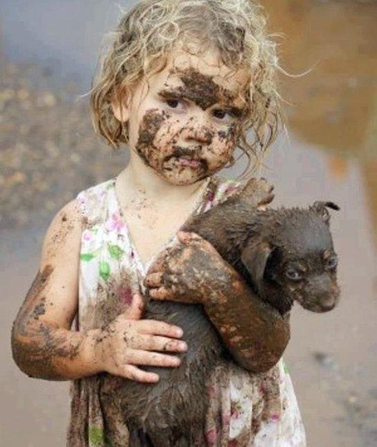 niña enlodada con el cachorro en sus brazos igual de sucio que ella