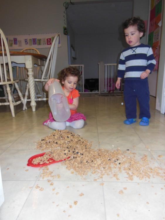 niña tira el cereal en el piso y hermano esta asustado