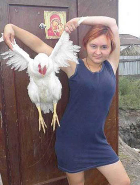 mujer posa con gallina de alas abiertas de forma sexy