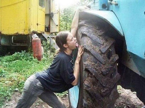 mujer tractor lamiendo llanta sucia con estiercol
