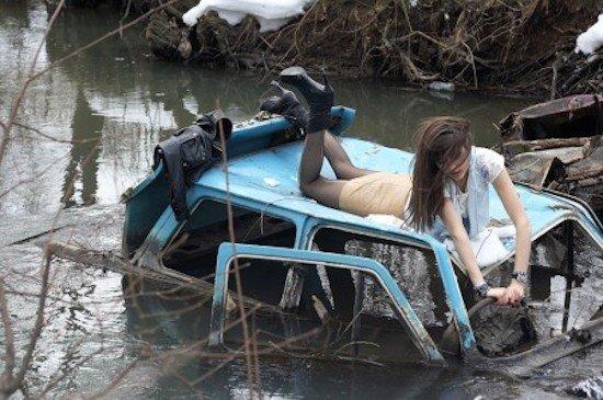 mujer posa en auto hundido en un río que le parece sexy
