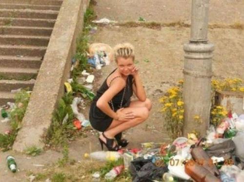 mujer posa junto a basura de forma sexy