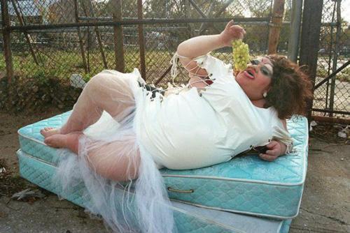 transexual posa en colchon mientras come uvas