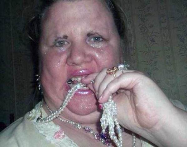 mujer mayor posa sexy mordiendo perlas