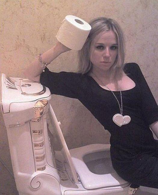 """mujer mostrando papel sanitario de forma """"sexy"""" sentada en la taza"""