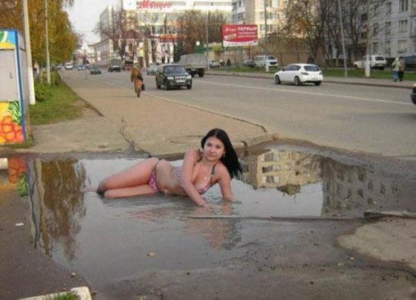 mujer posa en charco de agua por fuga en su vecindario