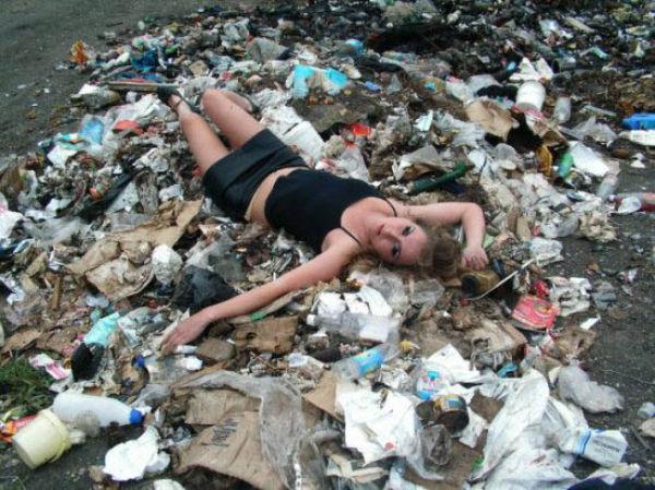 mujer recostada sobre la basura busca posar sexy