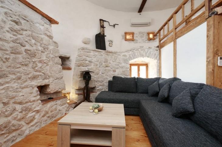 sala con paredes en piedra y sofa azul