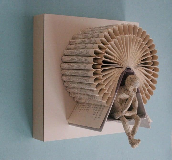 libro hecho arte con un hombre en rueda de hamster