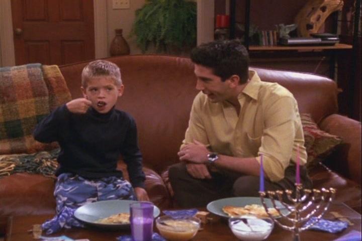 padre e hijo sentados en un sillón mientras cenan