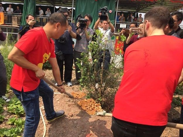 Matt Stopera junto al hermano naranjo excavando para plantar un árbol