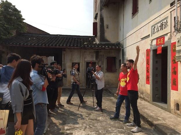 Matt Stopera junto al hermano naranja posando frente a la casa de un futbolista