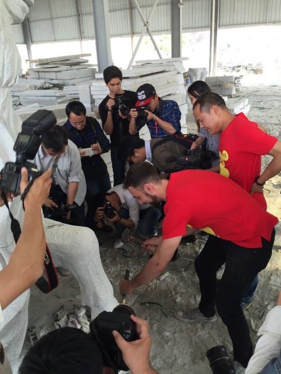 Matt Stopera rodeado de personas cincelando en una piedra