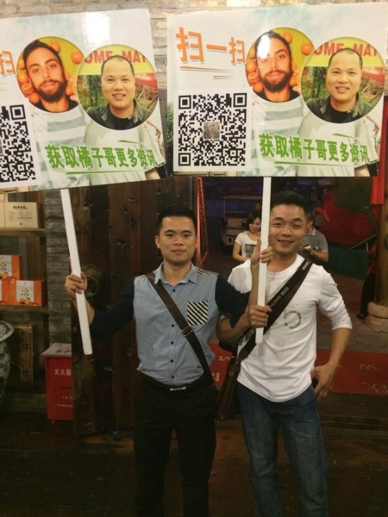 Chicos chinos con carteles de la cara de Matt Stopera y el hermano naranja