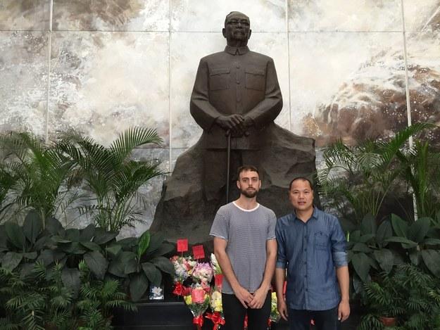 Matt Stopera y el hermano naranja frente la estatua de un líder comunista local