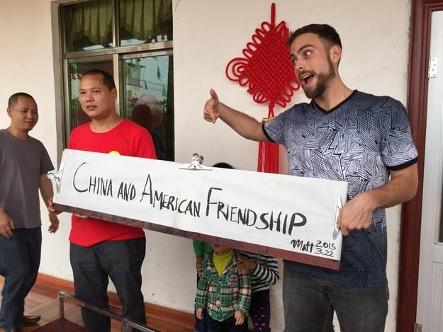 Matt Stopera y el hermano naranja sosteniendo un letrero que dice china y américa amigos