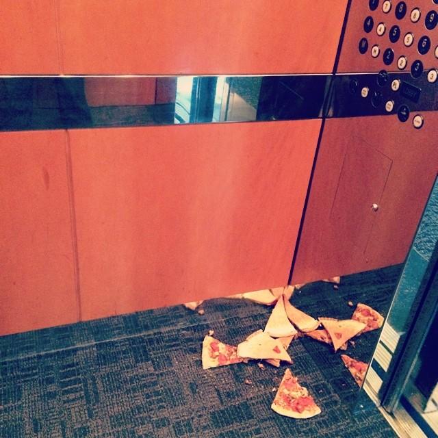 Pedazos de pizza tirados dentro de un elevador