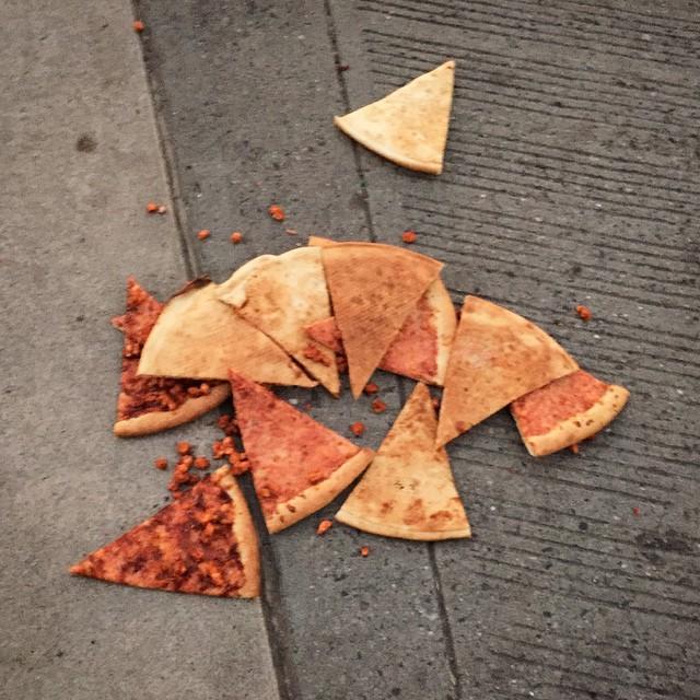 Pedazos de pizza tirados en el suelo