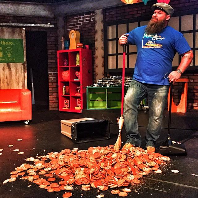 Hombre con una escoba sobre un montón de galletas en el suelo