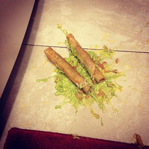 Taquitos en el suelo sobre una salsa verde