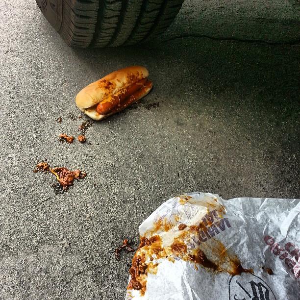 Hot dog en el suelo detrás de la llanta de un carro