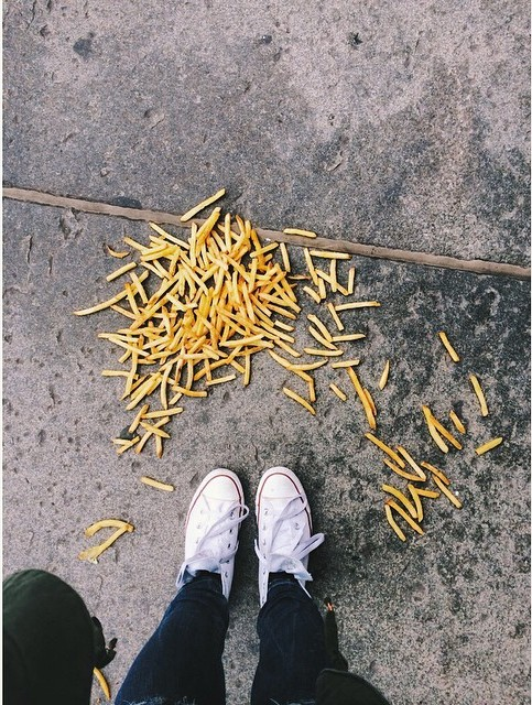 Papas fritas tiradas en el suelo frente a los pies de una persona