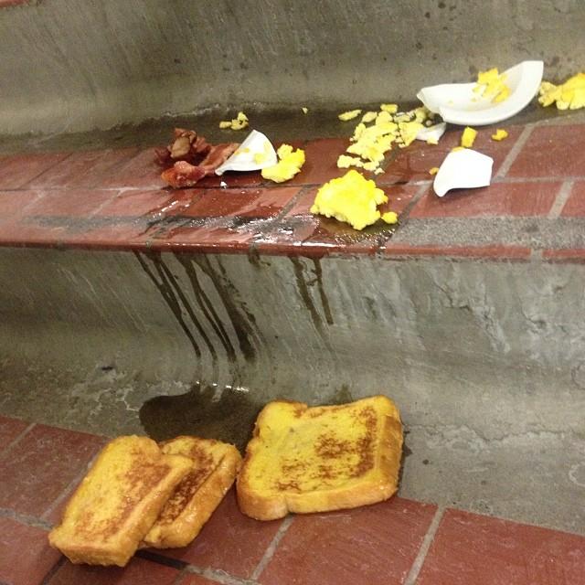 Desayuno de pan con tocino derramado en el piso