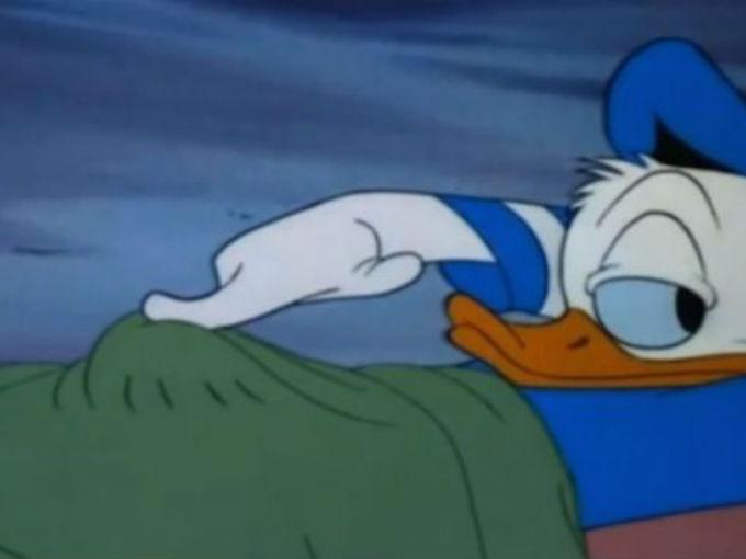 El pato donald acostado tocando algo que hay debajo de su cobija