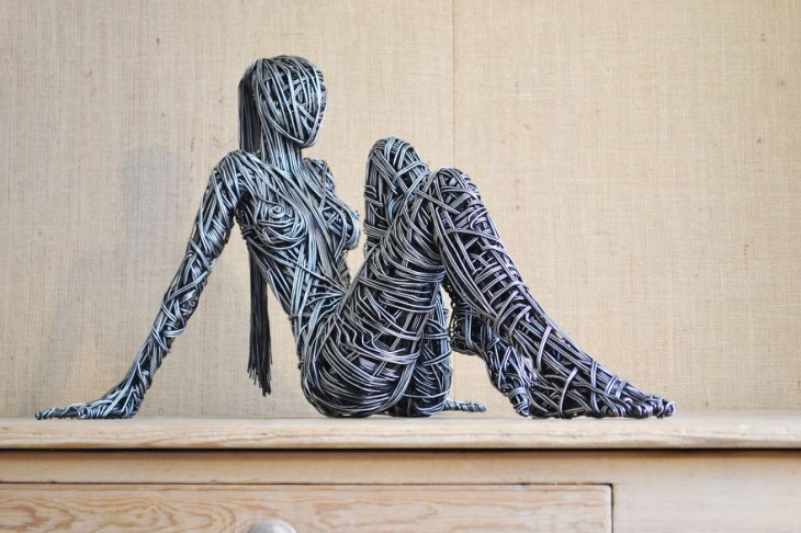 Escultura de una mujer sentada sobre un pedazo de madera