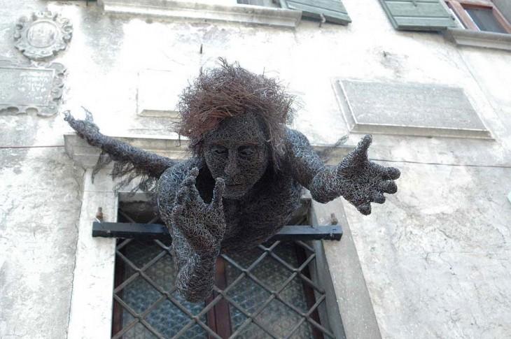 Escultura de alambre con la forma de un chico estirándose por una ventada de Mattia Trotta