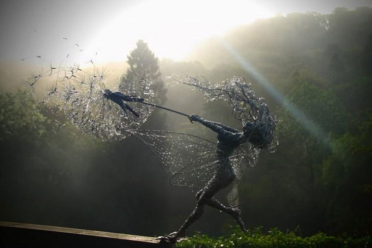 Escultura de hada hecha con alambre sosteniendo un diente de león